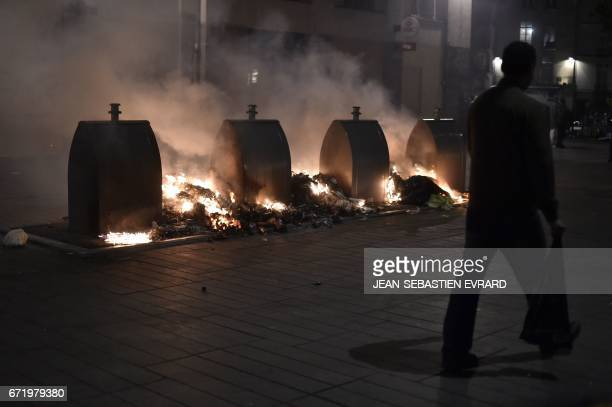 People walk past garbage set alight during clashes between antifascist demonstrators and antiriot police forces in Nantes western France on April 23...