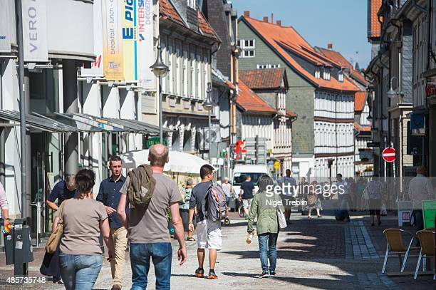 People walk past halftimbered houses typical of traditional central German historical towns on August 29 2015 in Goslar Germany Goslar town Mayor...