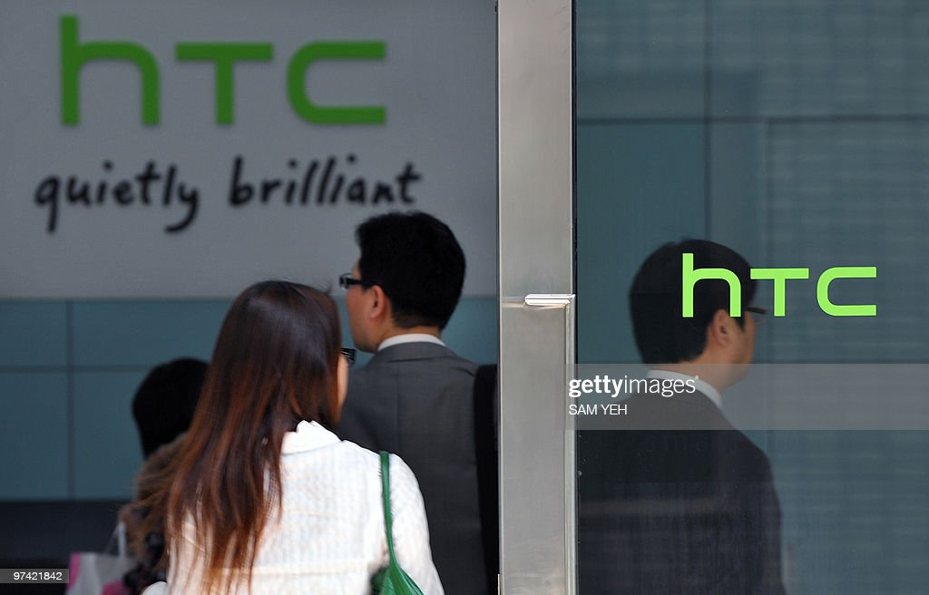 People walk past High Tech Computer Corp. (HTC) logos in Hsintien, Taipei county on March 3, 2010. Taiwan's leading smartphone maker High Tech Computer Corp. (HTC) denied infringing iPhone patents held by Apple after the US technology giant filed a lawsuit in the United States. AFP PHOTO / Sam YEH