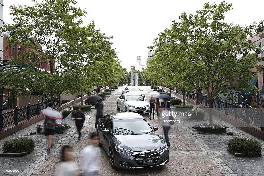 People walk past Honda Motor Co. Accord hybrid sedans as they are displayed during the unveiling in Tokyo, Japan, on Thursday, June 20, 2013. Honda, Japan's third-largest carmaker, unveiled a hybrid sedan at a 20 percent higher price than Toyota Motor Corp.'s gasoline-electric Camry, betting drivers will pay extra for fuel economy. Photographer: Kiyoshi Ota/Bloomberg via Getty Images