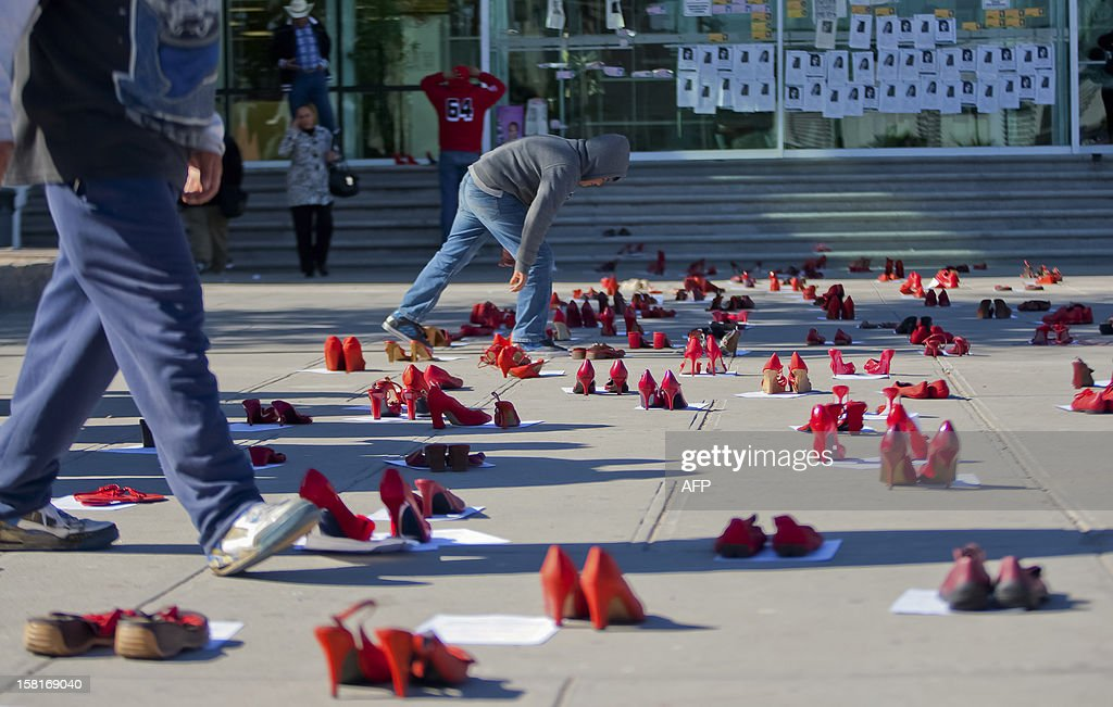 People walk past hundreds of red shoes symbolizing missing women in front of the State Attorney Office during a demo in Ciudad Juarez Mexico on...