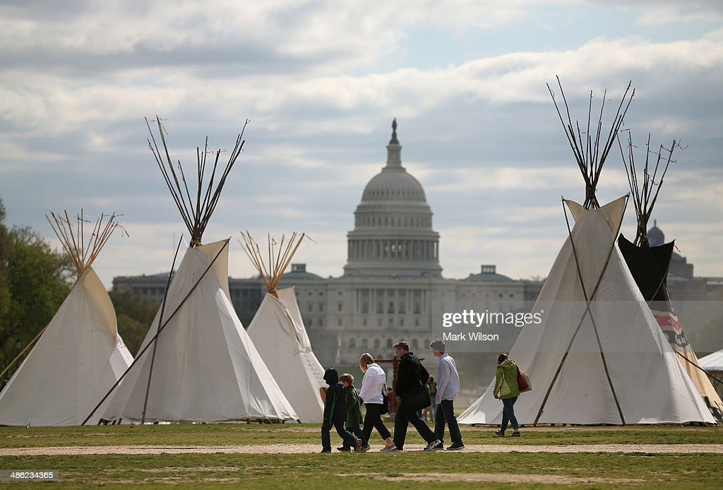 People walk past Indian Teepees that are on the National Mall as part of a protest against the Keystone pipeline April 23, 2014 in Washington, DC. As part of its 'Reject and Protect' protest, the Cowboy and Indian Alliance is organizing a weeklong series of actions by farmers, ranchers and tribes to show their opposition to the pipeline.