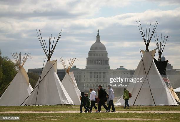 People walk past Indian Teepees that are on the National Mall as part of a protest against the Keystone pipeline April 23 2014 in Washington DC As...