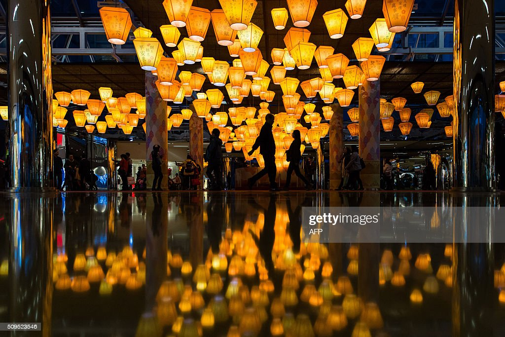 People walk past lanterns on display at a shopping centre to celebrate the Lunar New Year in Hong Kong on February 11, 2016. The Lunar New Year of the Monkey started on February 8. AFP PHOTO / DALE DE LA REY / AFP / DALE de la REY