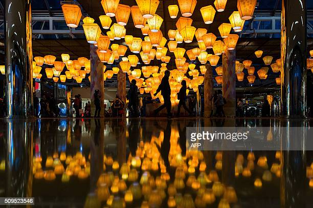 People walk past lanterns on display at a shopping centre to celebrate the Lunar New Year in Hong Kong on February 11 2016 The Lunar New Year of the...