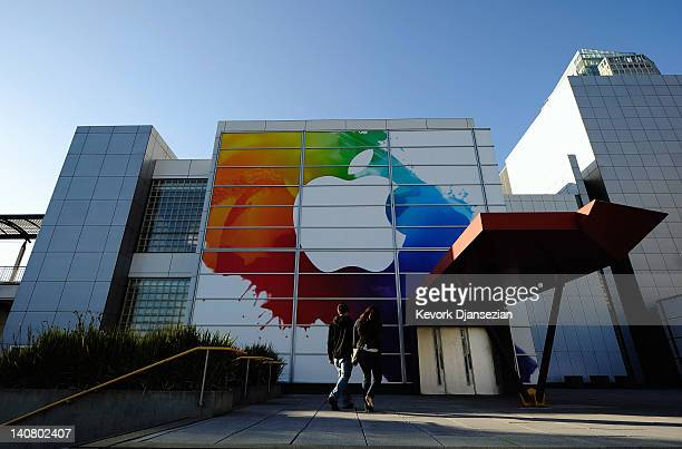 People walk past large Apple sign placed at the front entrance of the Yerba Buena Center for the Arts in preperation for the unveiling of the new...