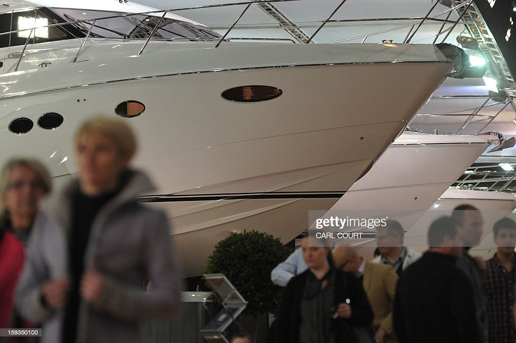 People walk past luxury motor boats on display at the 2013 London Boat Show in east London on January 12, 2013. The nine-day show features everything from speedboats to dinghies, boat paint to hot tubs with exhibits from many major marine and watersports related brands.