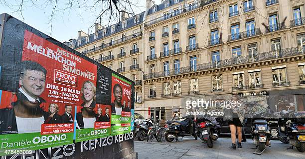 People walk past municipal election posters in Paris France on March 13 2014 According to the lasest public opinion research French Socialist party's...