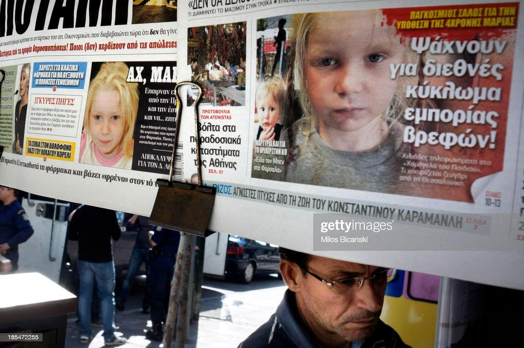 People walk past newspapers on a stand which feature front pages reporting on the story a four-year-old girl reportedly named Maria, who was found living with a Roma couple in central Greece, on October 21, 2013 in Athens, Greece. The Roma couple are due to appear in court today in Larissa, Greece, on charges of abducting the young girl, who was found on Wednesday October 16th, 2013, at a Roma settlement near Farsala in central during a police raid of the area for suspected drug trafficking.