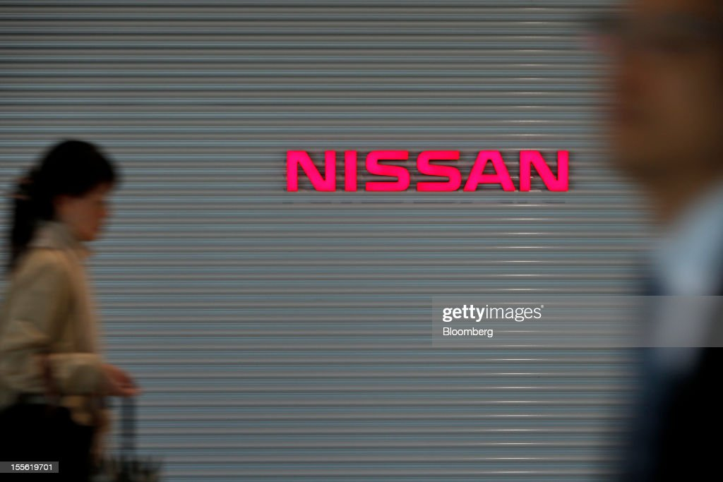 People walk past Nissan Motor Co. signage at the company's headquarters in Yokohama City, Kanagawa Prefecture, Japan, on Tuesday, Nov. 6, 2012. Nissan, the top Japanese seller of vehicles in China, cut its full-year net income forecast 20 percent after consumer backlash stemming from a territorial dispute sent sales lower in its largest market. Photographer: Kiyoshi Ota/Bloomberg via Getty Images