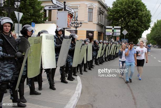 People walk past officers the Russian riot police force OMON blocking a street in the Crimean capital Simferopol on May 17 2014 ahead of the 70th...