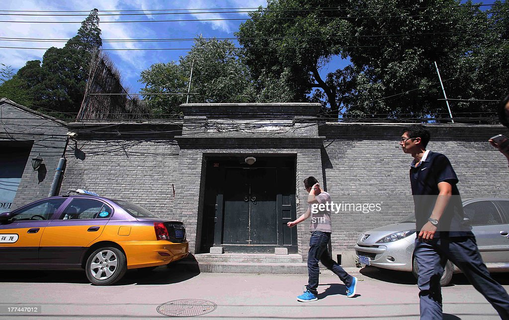 People walk past one of the houses that belongs to fallen Chinese political star Bo Xilai and his family in Beijing on August 23, 2013. The trial of fallen Chinese politician Bo Xilai, which had been widely expected to last no more than two days, will continue into a third day on August 24, the court said. Bo, once one of China's highest-flying politicians, faces charges of bribery, embezzlement and abuse of power which emerged after the lurid scandal triggered by the death of British businessman Neil Heywood. CHINA OUT AFP PHOTO