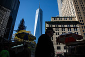 People walk past One World Trade Center which opens today on November 3 2014 in New York City The skyscraper is 104 stories tall and cost $39 billion...
