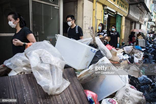 People walk past piles of debris and rubbish on a street in the aftermath of Typhoon Hato in Macau on August 26 2017 The Chinese army on August 25...