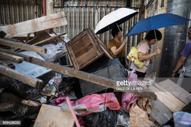 TOPSHOT People walk past piles of debris and rubbish on a street in the aftermath of Typhoon Hato in Macau on August 26 2017 The Chinese army on...