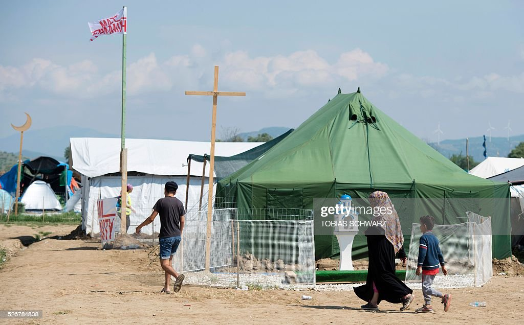 People walk past places for prayer at a makeshift camp for migrants and refugees near the village of Idomeni not far from the Greek-Macedonian border on May 1, 2016. Some 54,000 people, many of them fleeing the war in Syria, have been stranded on Greek territory since the closure of the migrant route through the Balkans in February. / AFP / TOBIAS