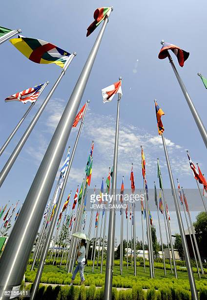 People walk past poles displaying national flags of some of the participating Olymjpic countries at the Olympic Village in Beijing on August 2 2008...