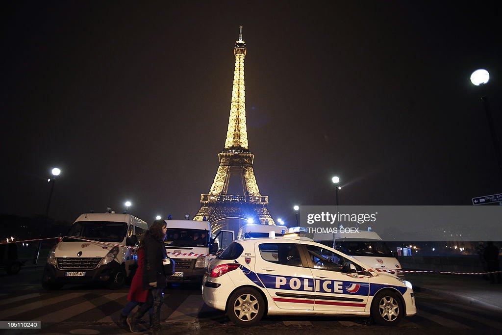People walk past police cars blocking the way to the Eiffel Tower in Paris on March 30, 2013. The Eiffel Tower was evacuated in the evening on March 30 after an anonymous phone call announced an attack, according to a police source. The perimeter of the monument was secured and about 1,400 people were evacuated shortly before 21h00.