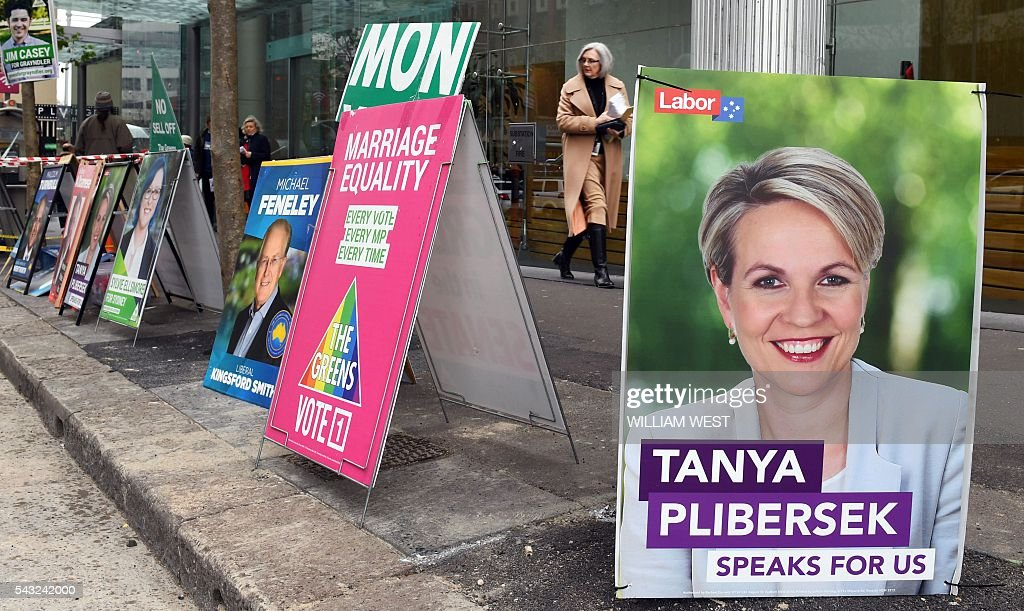 People walk past political placards outside a polling station in Sydney's central business district on June 27, 2016, which is open to voters who will be absent on election day. Australia's ruling party on June 27 used the Brexit vote to warn against voting for Labor in upcoming elections as a poll showed the Liberals ahead for the first time in a drawn-out campaign. WEST