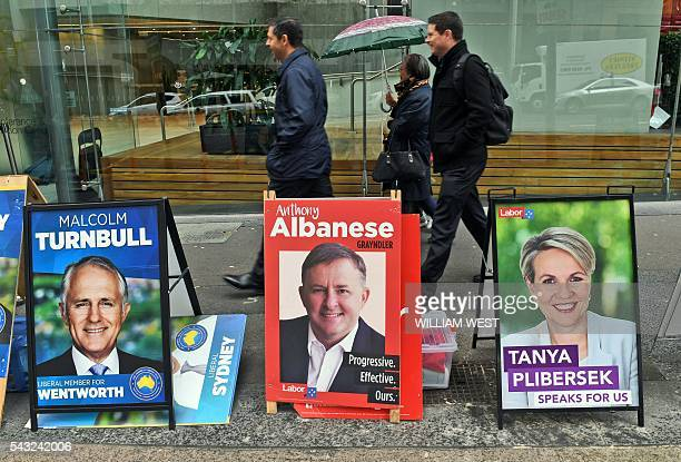 People walk past political placards outside a polling station in Sydney's central business district on June 27 which is open to voters who will be...