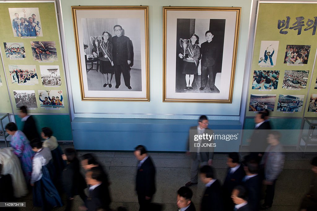 People walk past portraits of former North Korean leaders Kim Il-Sung and Kim Jong-Il which are displayed at a theatre during celebrations to mark the 100th birth anniversary of the country's founding leader Kim Il-Sung, in Pyongyang on April 16, 2012. The commemorations came just three days after a satellite launch timed to mark the centenary fizzled out embarrassingly when the rocket apparently exploded within minutes of blastoff and plunged into the sea. AFP PHOTO / Ed Jones