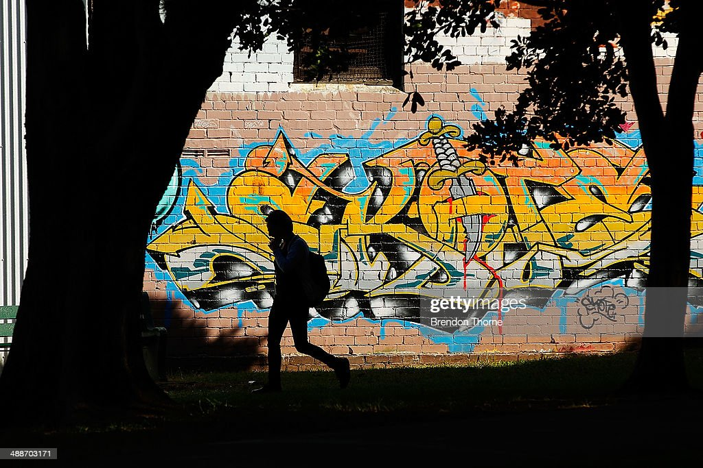 People walk past properties strewn with graffiti on May 8, 2014 in Sydney, Australia. The Grafitti Control Amendment Act passed in the NSW legislative council yesterday includes tougher penalties a the ability for local courts to enforce community clean up duty on offenders.