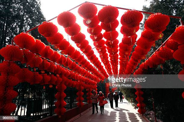 People walk past red lanterns during the Ditan Temple Fair opened today to celebrate the lunar New Year of the Tiger on February 13 2010 in Beijing...