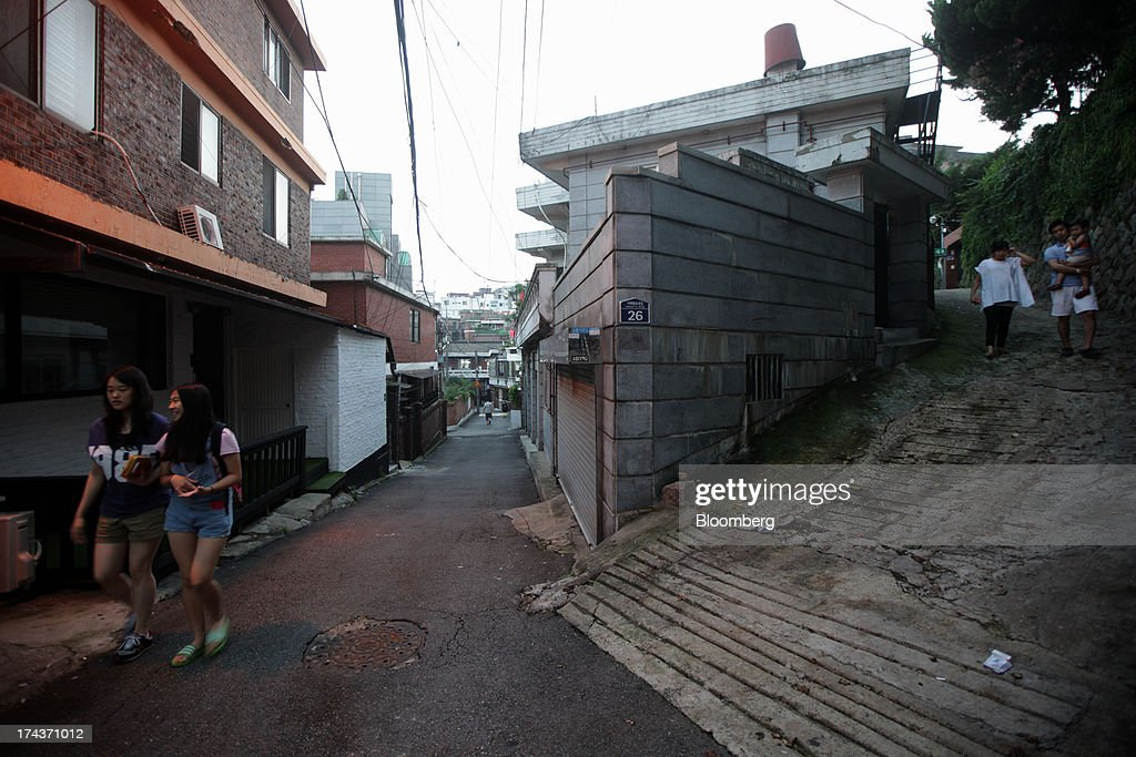 People walk past residential buildings in the area of Hannam-dong in Seoul, South Korea, on Wednesday, July 24, 2013. South Koreas economy grew the most in more than two years, on stronger government spending and private consumption even as a slowdown in China clouds the outlook. Photographer: Woohae Cho/Bloomberg via Getty Images