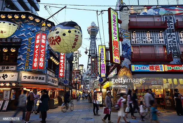 People walk past restaurants illuminated at dusk as the Tsutenkaku tower center stands in the Shinsekai shopping district of Osaka Japan on Friday...