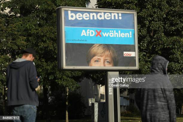 People walk past rotating billboards that show an election campaign poster of German Chancellor and Christian Democrat Angela Merkel intersecting...