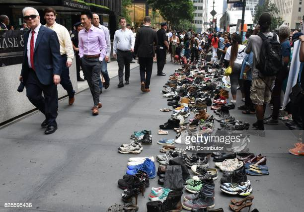 People walk past rows of shoes placed in front of JPMorgan Chase on park Avenue in New York on August 2 2017 during a protest by immigrants and...