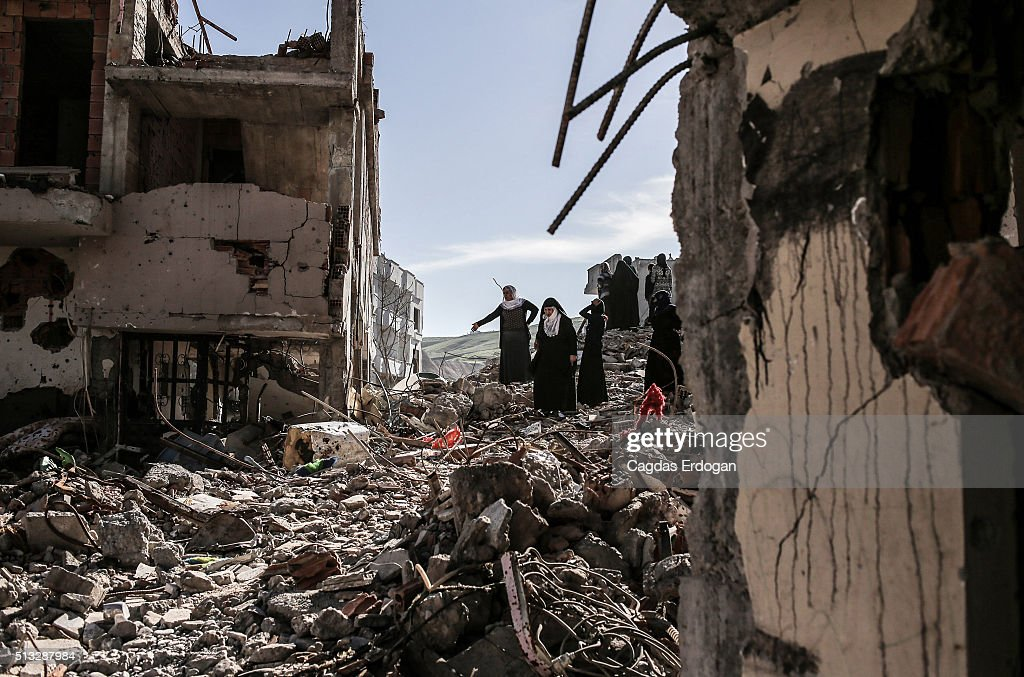 People walk past ruined houses and shops in Cizre March 2 Turkey Turkish authorities scaled down a 24hour curfew imposed on the mainly Kurdish town...