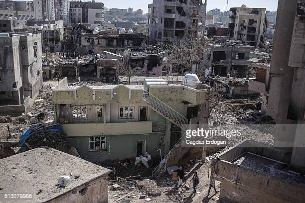 People walk past ruined houses and shops on March 2 2016 in Cizre Turkey Turkish authorities scaled down a 24hour curfew imposed on the mainly...