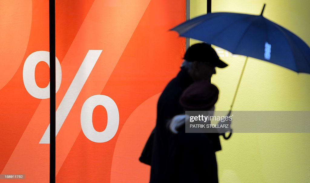People walk past sale advertisement in shop window on January 3, 2013 in Essen, western Germany. Official start of the winter sale in Germany is on January 4, 2013. AFP PHOTO / PATRIK STOLLARZ
