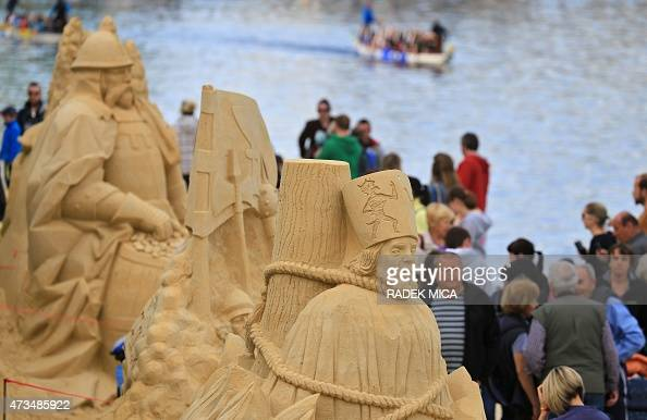 People walk past several sand sculptures presented in Pisek South Bohemia Czech Republic on May 15 2015 The sculptures featuring among others Czech...