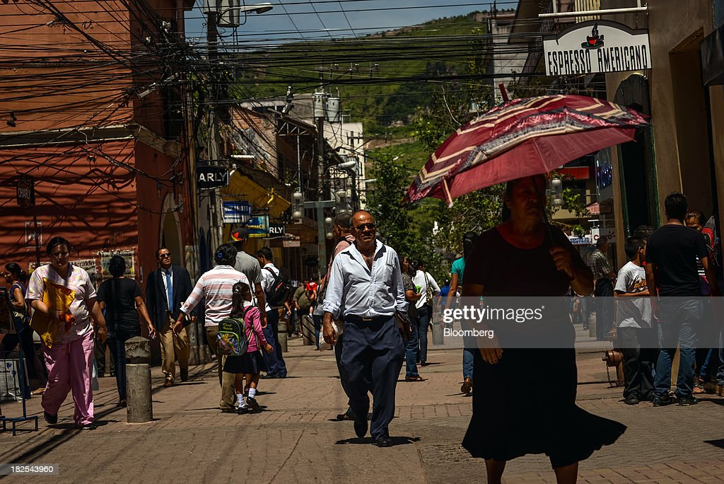 People walk past shops in downtown Tegucigalpa Honduras on Thursday Sept 5 2013 Economic growth in Honduras is forecast to slow to 3 percent this...
