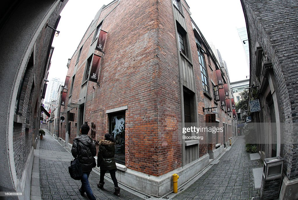 People walk past shops in the Shanghai Xintiandi precinct, a project developed by Shui On Land Ltd., in this photograph taken with a fish-eye lens in Shanghai, China, on Wednesday, Feb. 6, 2013. China's economic growth accelerated for the first time in two years as government efforts to revive demand drove a rebound in industrial output, retail sales and the housing market. Photographer: Tomohiro Ohsumi/Bloomberg via Getty Images