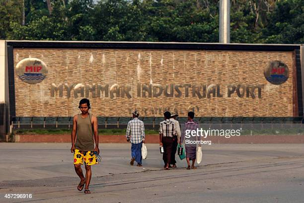 People walk past signage at an entrance to the Myanmar Industrial Port in Yangon Myanmar on Tuesday Oct 14 2014 Myanmars economy is set to grow more...
