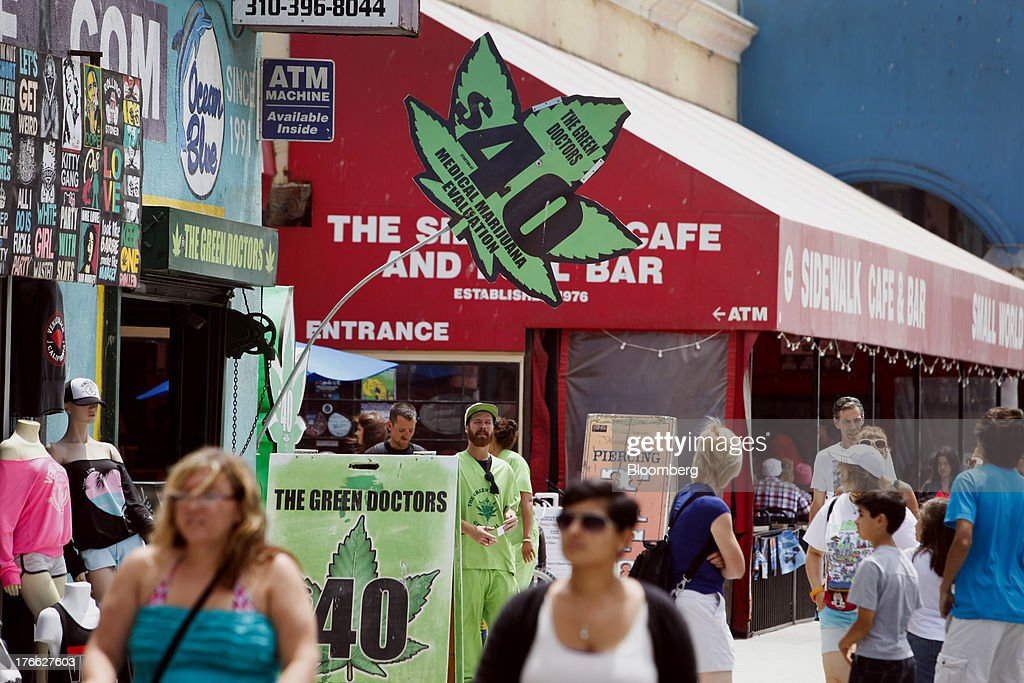 People walk past signs advertising 'Green Doctors' medical marijuana evaluations at Venice Beach in Los Angeles, California, U.S., on Wednesday, Aug. 14, 2013. Overall U.S. tourism-related sales increased 6.8% in the second quarter of 2013 as compared to 2012. Photographer: Patrick T. Fallon/Bloomberg via Getty Images