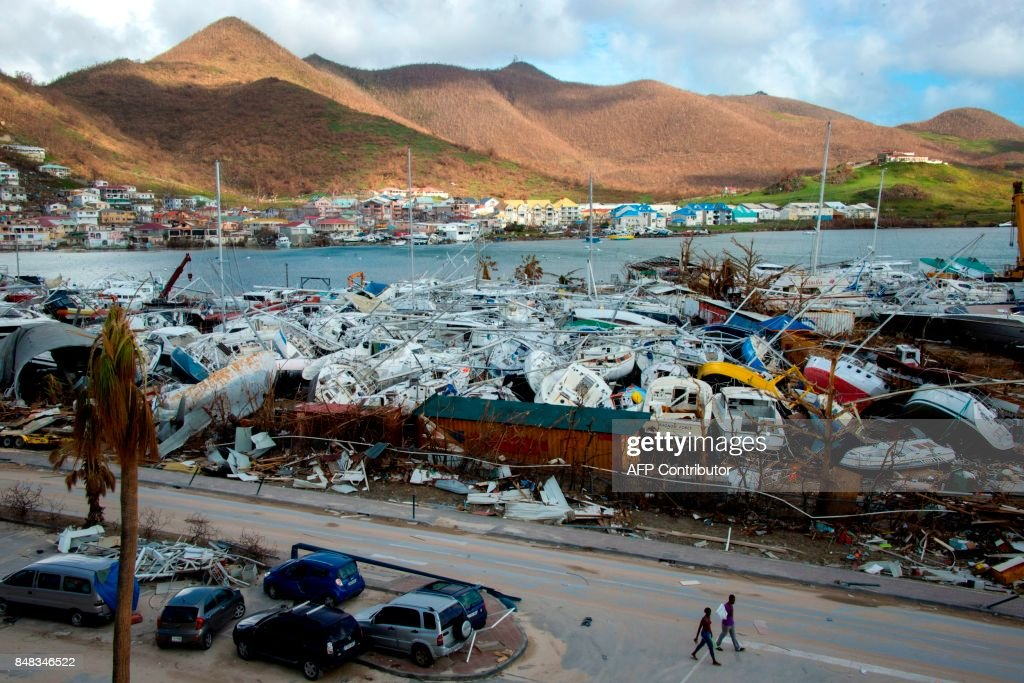 TOPSHOT - People walk past smashed boats on September 16, 2017 at Marigot shipyard on the French Caribbean island of Saint Martin after the island was hit by Hurricane Irma. The Caribbean island of St Martin was a place of spectacular inequalities before Hurricane Irma flattened rich and poor neighbourhoods alike -- but some residents now dream of a fresh start. Ten days after the storm devastated the island, cleaning up and reconstruction remain a priority for St Martin, although repairing roads and buildings before the high season, which usually starts in November and runs until April, seems nearly impossible. / AFP PHOTO / Helene Valenzuela