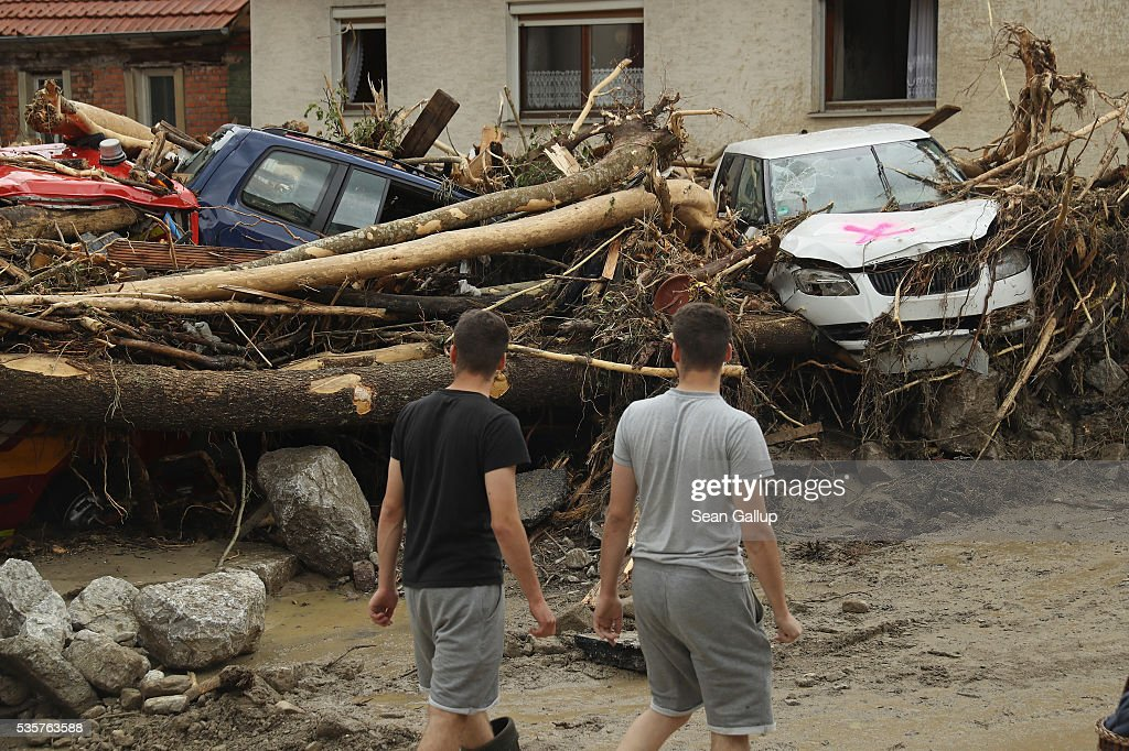 People walk past smashed trees, cars and other debris that cover a street in the village center following a furious flash flood the night before on May 30, 2016 in Braunsbach, Germany. The flood tore through Braunsbach, crushing cars, ripping corners of houses and flooding homes during a storm that hit southwestern Germany. Miraculously no one in Braunsbach was killed, though three people died as a result of the storm in other parts of the country.