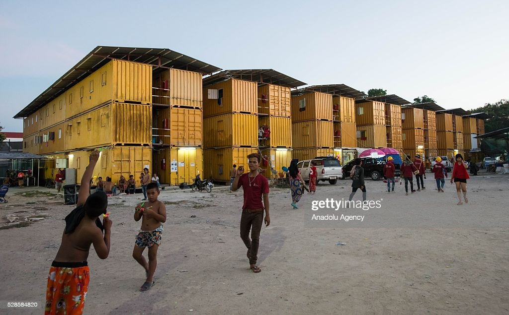 People walk past steel containers at a construction workers' camp on May 6, 2016 in Bangkok, Thailand. Mainly migrants from neighboring countries, like Cambodia and Laos, live in this camp, which has grocery shops, a common washing area and even a small school, on the outskirts of Bangkok.
