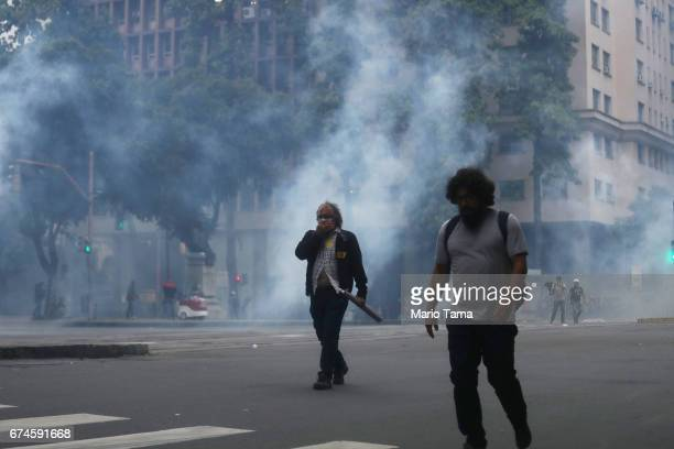People walk past tear gas launched towards protestors by police during a nationwide general strike on April 28 2017 in Rio de Janeiro Brazil The...