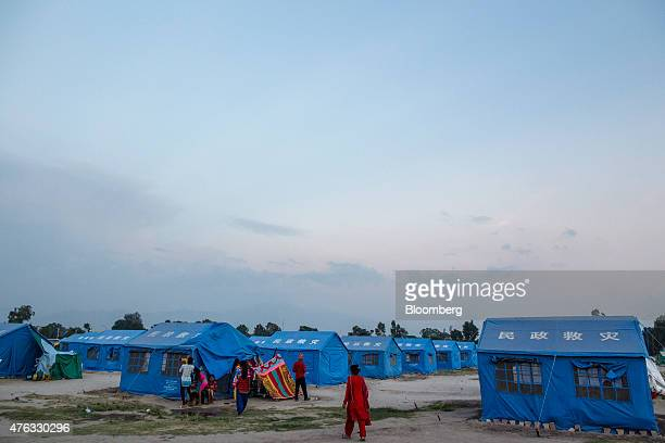People walk past tents at an internal displacement camp at the Tudikhel field in Kathamandu Nepal on Wednesday June 3 2015 Nepal's gross domestic...