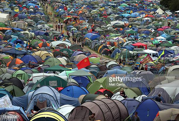 People walk past tents at the Glastonbury Festival of Contemporary Performing Arts site at Worthy Farm Pilton on June 27 2013 near Glastonbury...