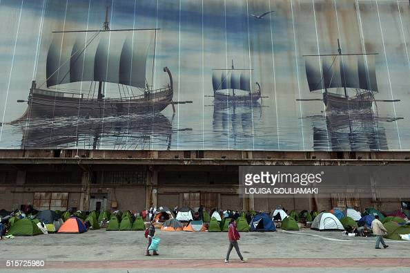 People walk past tents set up at the port of Piraeus near Athens where thousands of stranded refugees and migrants have found a temporary shelter on...