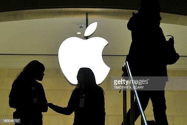 People walk past the Apple logo at the Apple Store at Grand Central Terminal in New York ON January 25 2013 Apple shares slid about 12 percent on...