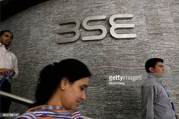 People walk past the Bombay Stock Exchange logo displayed outside the building's lobby in Mumbai India on Thursday Jan 23 2014 Indian stocks dropped...