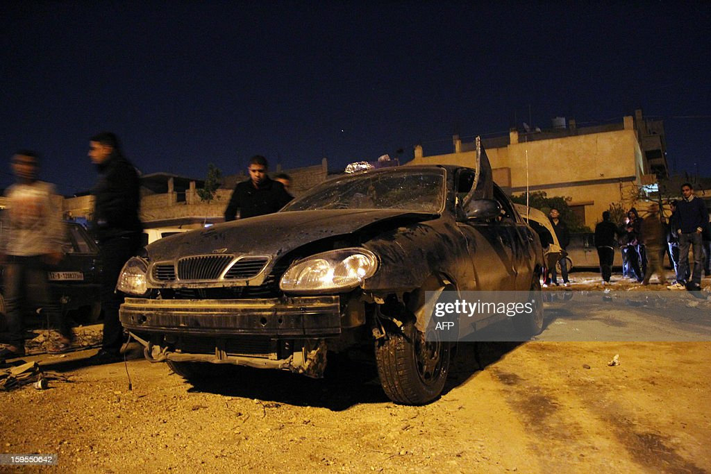 People walk past the car of a police officer after it exploded in the eastern Libyan city of Benghazi late on January 15, 2013. A car bomb killed a police officer, an official said, the latest violence to hit the cradle of the 2011 revolt that ousted dictator Moamer Kadhafi. AFP PHOTO/Abdullah DOUMA