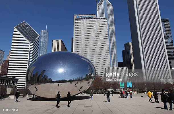 People walk past the Cloud Gate sculpture aka 'The Bean' as One Prudential Plaza is seen over the north end of Millennium Park on March 28 2011 in...